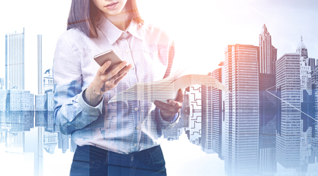 Unrecognizable young businesswoman standing with phone and documents over cityscape background. Concept of communication. Toned image double exposure