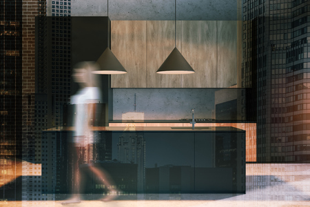 Young woman walking in concrete and brick kitchen with wooden countertops and black island with built in sink. Toned image double exposure blurred