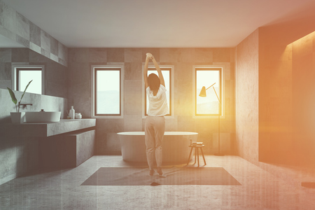 Rear view of young woman standing in modern bathroom interior with tiled walls, stone floor, comfortable tub and sink and shower stall. Toned image double exposure