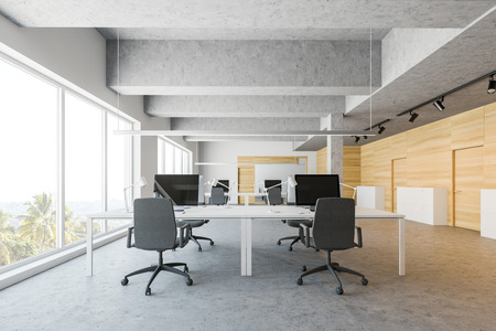 Interior of open space office with white and wooden walls, concrete floor and rows of large white computer tables. Closed doors and file cabinets. 3d rendering