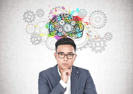 Thoughtful young Asian man in suit and glasses sitting near concrete wall with colorful brain with gears drawn on it. Concept of brainstorming. Stock Photo