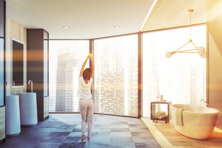 Rear view of young woman standing in panoramic bathroom with cityscape. Comfortable bathtub and double sink with mirrors. Toned image