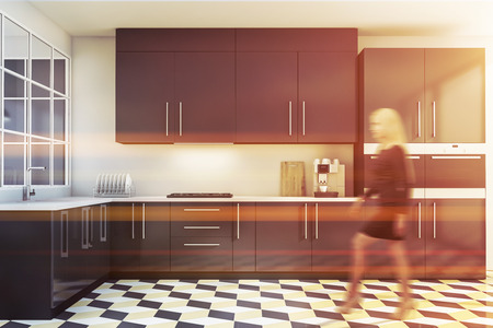 Blonde young woman walking in stylish white kitchen interior with tiled floor and gray countertops and cupboards. Toned image blurred