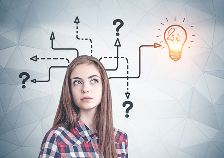 Thoughtful young woman in casual clothes standing near geometric pattern wall with question marks and lightbulb drawn on it. Concept of good idea