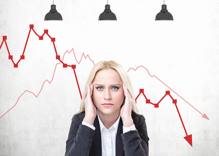 Stressed blonde woman in suit sitting near concrete wall with falling graphs drawn on it. Concept of financial crisis Stock Photo