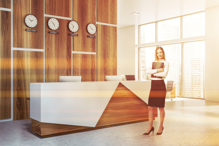 Smiling blonde businesswoman with folder standing near office reception desk with computers and clocks showing world time. Toned image