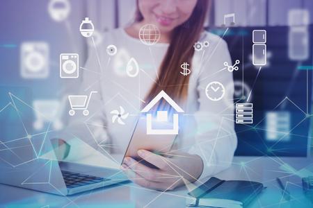 Lächelnde Frau in verschwommenem Büro mit Smartphone mit Doppelbelichtung von leuchtenden Smart-Home-Schnittstellensymbolen und Netzwerkhologramm. Getöntes Bild
