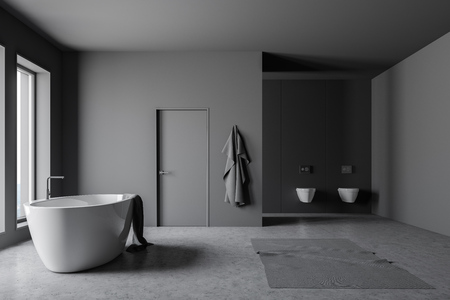 Corner of loft bathroom with dark gray walls, concrete floor and white bathtub with towel on it standing under windows. Door in the wall and two toilets. 3d rendering Stock Photo