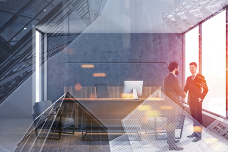 Two young businessmen shaking hands in modern CEO office with concrete and tray walls, computer table and coffee table with armchairs. Concept of partnership. Toned image double exposure
