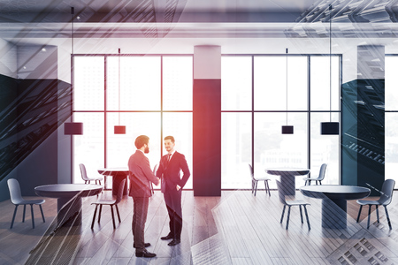 Two young businessmen shaking hands in modern cafe interior with green and white walls, panoramic windows and round tables with chairs. Toned image double exposure Imagens - 124678054
