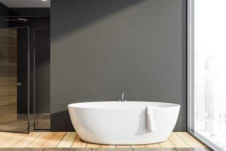 Interior of modern bathroom with dark gray walls, wooden floor, comfortable white bathtub standing near panoramic window and shower stall with glass doors. 3d rendering Stock Photo