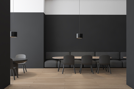 Interior of modern restaurant with black and white walls, wooden floor, gray sofas and chairs standing near round and wooden tables and stylish lamps. 3d rendering