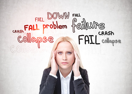 Stressed blonde woman in suit sitting near concrete wall with failure words written on it. Concept of crisis and problems