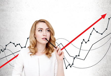 Thinking beautiful woman with red hair wearing smart casual clothes sitting near concrete wall with growing graphs. Concept of business growth and financial success.
