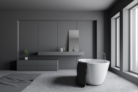 Side view of loft bathroom with dark gray walls, concrete floor, white bathtub standing near two windows and gray sink with mirror. 3d rendering Stock Photo
