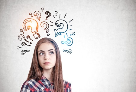Thoughtful young woman in casual clothes standing near concrete wall with question marks drawn on it. Concept of research. Mock up Banque d'images - 124680595