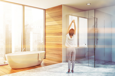 Rear view of young woman standing in luxury bathroom interior with white and wooden walls, panoramic window, comfortable bathtub and shower stall with glass walls. Toned image Stock Photo