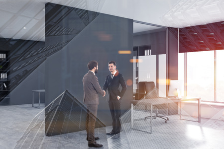 Two young businessmen shaking hands in CEO office with gray walls, panoramic window and gray computer table. Concept of partnership. Toned image double exposure Imagens - 124681275