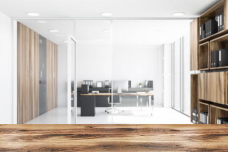 Blurred interior of CEO office with white walls, tiled floor, wooden computer desk and bookcase with folders in the hall. Table for your product in foreground. 3d rendering