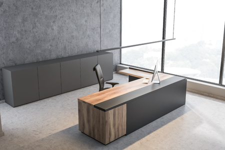 Corner of panoramic CEO office with concrete walls and floor, gray and wooden computer table and gray cabinets. 3d rendering