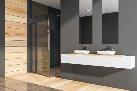 Corner of modern bathroom with dark gray and wooden walls, wooden and tiled floor, two sinks standing on white countertop with vertical mirrors above it and shower stall with glass door. 3d rendering Stok Fotoğraf - 124681855