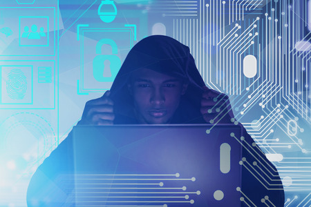Serious African American hacker in hoodie looking at laptop. Double exposure of circuit and online security interface. Toned image Stock Photo
