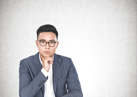 Portrait of young handsome thoughtful Asian man in suit and glasses looking forward and thinking with his hand on chin. Concrete wall background. Concept of brainstorming and business. Mock up Banco de Imagens