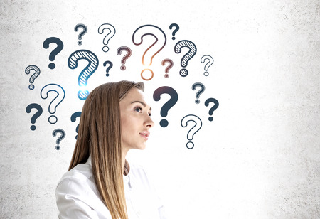 Thoughtful young woman in white shirt standing near concrete wall with empty question marks drawn on it. Concept of looking for answer