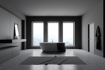 Interior of loft bathroom with dark gray walls, concrete floor, white bathtub standing near three windows and gray sink with mirror. 3d rendering Stock Photo