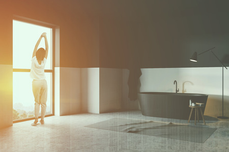 Rear view of woman in pajamas standing in white and black bathroom corner with concrete floor, black bathtub and rug on the floor. Toned image double exposure Stock Photo