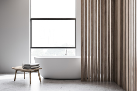 Interior of minimalistic bathroom with white and wooden walls, concrete floor, loft window with white bathtub standing under it and wooden chair with towels and shampoos. 3d rendering