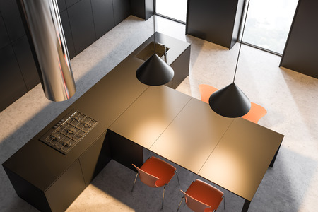 Top view of stylish kitchen with black walls, concrete floor, black island with built in sink and cooker and black table with orange chairs. 3d rendering