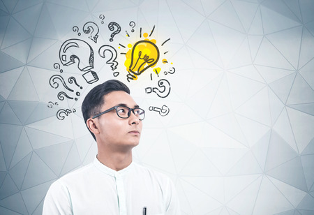 Portrait of serious young Asian businessman in glasses and white shirt standing near geometric pattern wall with question marks and lightbulb drawn on it. Concept of good idea. Mock up