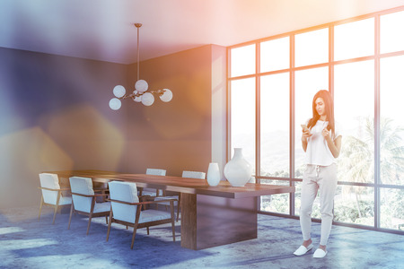 Young woman with phone and coffee standing in panoramic dining room with gray walls, concrete floor and wooden table with armchairs. Toned image