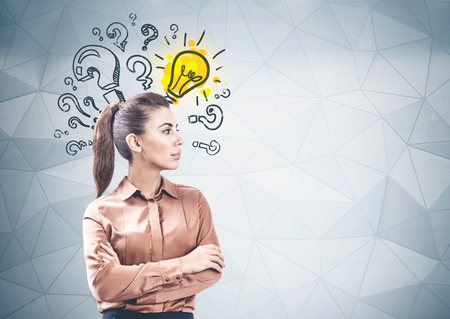 Portrait of confident businesswoman standing with crossed arms near geometric pattern wall with question marks and lightbulb on it. Concept of research. Mock up Reklamní fotografie