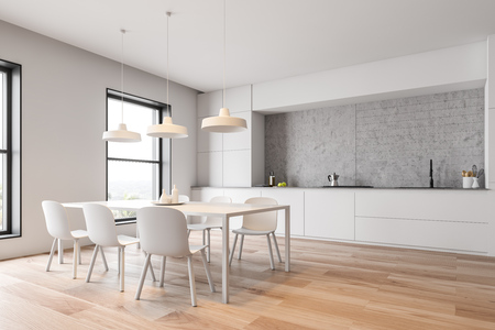 Corner of modern kitchen with concrete and white walls, wooden floor, white cupboards and countertops with built in sink and cooker and white table with chairs. 3d rendering