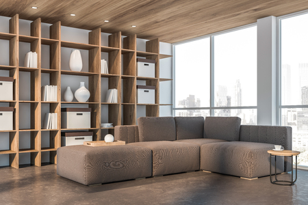 Corner of minimalistic living room with white walls, concrete floor, wooden ceiling, brown sofa with little coffee table and wooden bookcase. 3d rendering