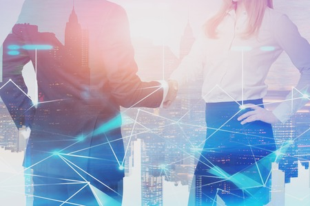 Unrecognizable businessman and blonde businesswoman shaking hands in city with double exposure of network hologram. Concept of technology and partnership. Toned image