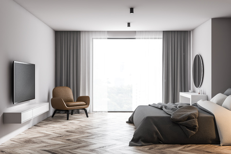 Side view of panoramic bedroom with white walls, wooden floor, gray master bed with makeup table and modern TV on the wall. Comfortable leather armchair. 3d rendering Standard-Bild - 124703336