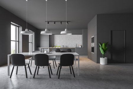 Interior of modern kitchen with gray and concrete walls, concrete floor, gray countertops and bar with stools. Two built in ovens and table with chairs. 3d rendering