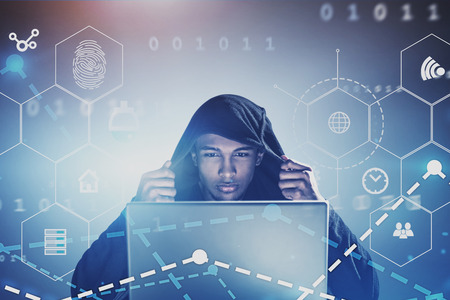 Serious young hacker in black hoodie looking at his laptop screen with double exposure of online security interface. Concept of identity theft and information protection. Toned image double exposure Stock Photo