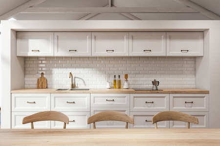 Close up of wooden table with chairs standing in Scandinavian kitchen with white walls and white countertops with built in sink and cooker. 3d rendering