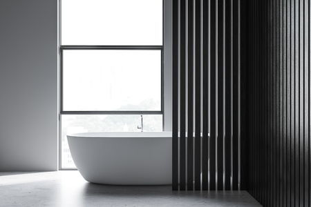 Interior of minimalistic bathroom with white and dark wooden walls, concrete floor and loft window with white bathtub standing under it. 3d rendering