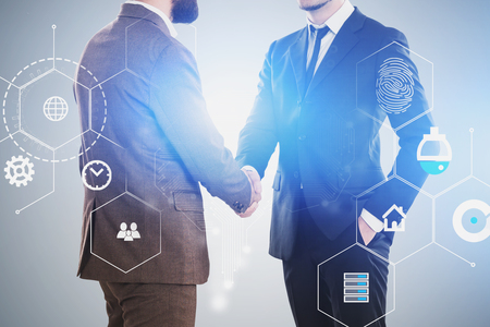 Two unrecognizable businessmen shaking hands over gray background with double exposure of digital business interface. Concept of IoT and smart home. Toned image Imagens - 124703949
