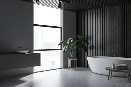 Corner of modern bathroom with gray and dark wooden walls, concrete floor, white bathtub and sink on gray counter with window near it. 3d rendering