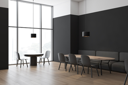 Corner of modern restaurant with black and white walls, wooden floor, gray sofas and chairs standing near round and wooden tables and big window. 3d rendering