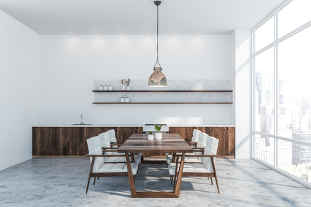 Interior of modern kitchen with white walls, concrete floor, dark wooden countertops with built in sink and oven and wooden table with white armchairs. 3d rendering Imagens