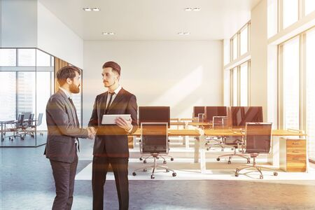 Two businessmen shaking hands in modern white open space office with rows of wooden computer tables and meeting room in background. Toned image