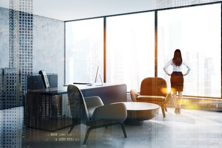 Businesswoman standing in panoramic CEO office with concrete walls, massive computer table and armchairs near coffee table. Concept of leadership. Toned image double exposure