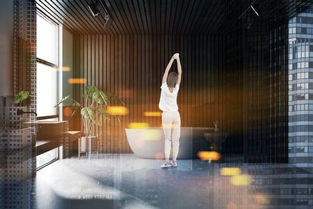 Rear view of woman in pajamas standing in stylish bathroom interior with white and wooden walls, concrete floor, white bathtub and double sink. Toned image double exposure Reklamní fotografie - 124803713